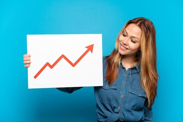 Девушка-подросток на изолированном синем фоне держит табличку с растущим символом стрелки статистики со счастливым выражением лица
