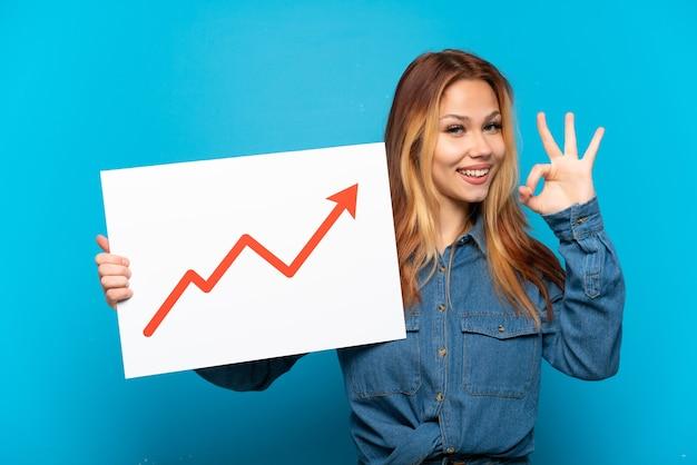 孤立した青い背景上の 10 代の少女 ok サインで成長している統計矢印記号で看板を持っている