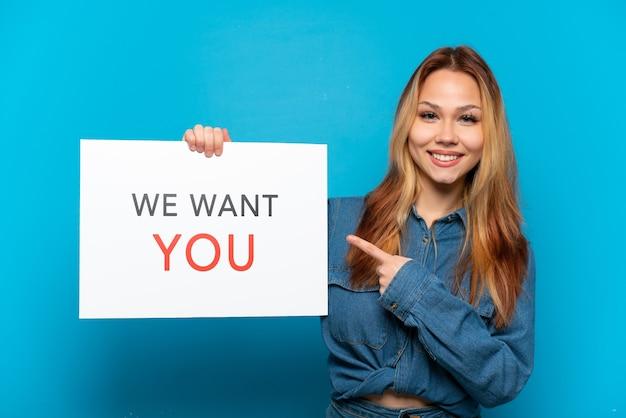 Девушка-подросток на изолированном синем фоне держит доску we want you и указывает на нее