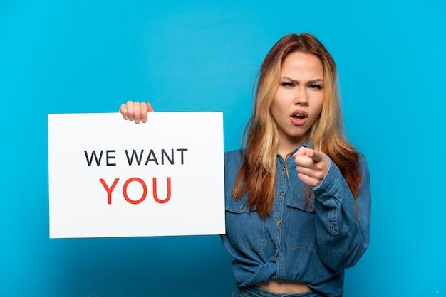 Девушка-подросток на изолированном синем фоне держит доску we want you и указывает вперед
