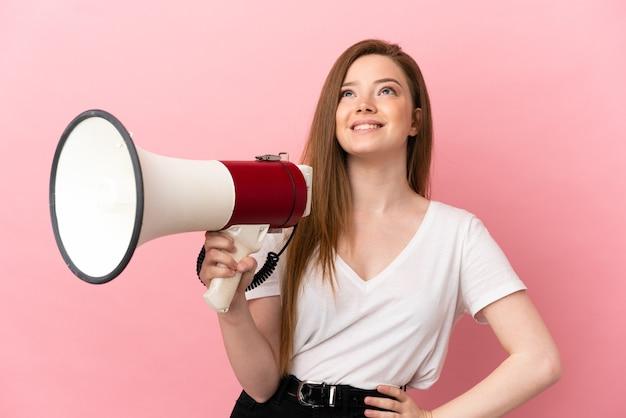 Девушка-подросток на изолированном розовом фоне держит мегафон и смотрит вверх, улыбаясь