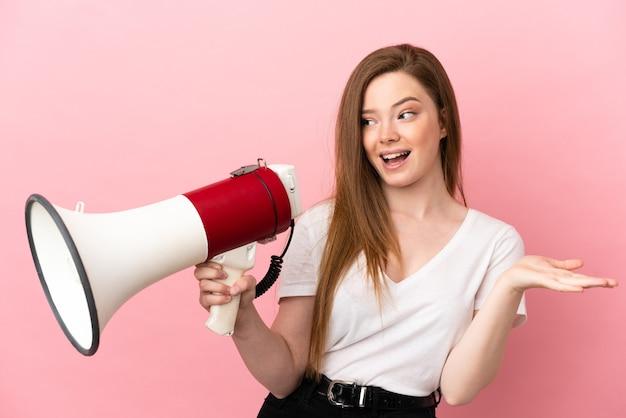 Девушка-подросток на изолированном розовом фоне держит мегафон и с удивленным выражением лица