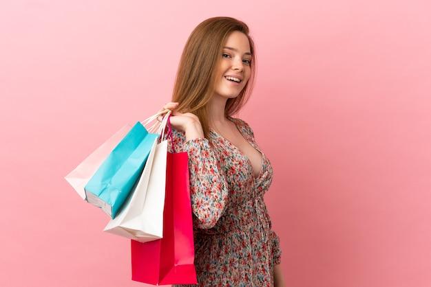 ショッピングバッグを保持し、笑顔の孤立したピンクの背景上のティーンエイジャーの女の子
