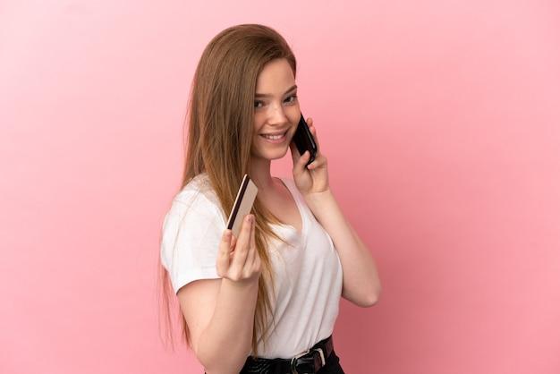 격리된 분홍색 배경 위에 있는 10대 소녀는 휴대전화와 대화를 유지하고 신용 카드를 들고 있습니다.