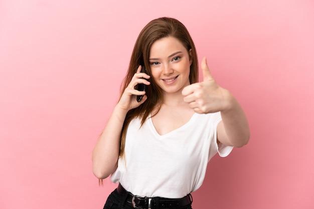 Девушка-подросток на изолированном розовом фоне поддерживает разговор с мобильным телефоном и показывает палец вверх