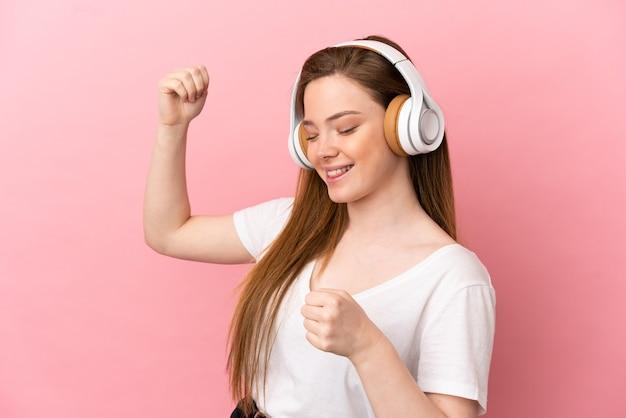 Девушка-подросток на изолированном розовом фоне, слушает музыку и танцует