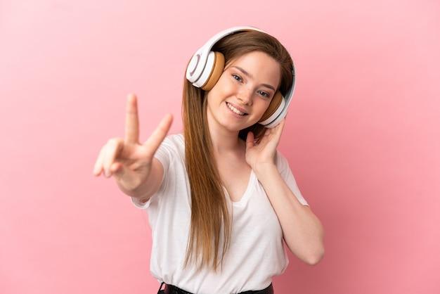 Девушка-подросток на изолированном розовом фоне, слушает музыку и поет