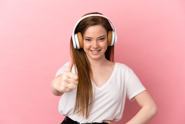 孤立したピンクの背景の上のティーンエイジャーの女の子が音楽を聴いて、親指を立てて