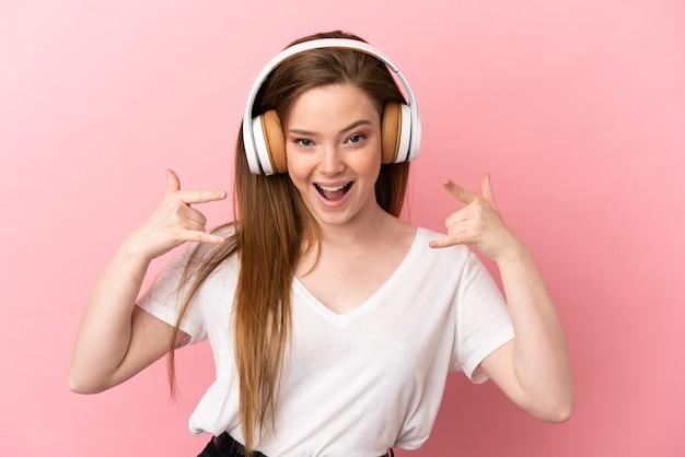 Девушка-подросток на изолированном розовом фоне, слушая музыку, делая рок-жест