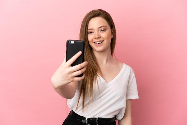 携帯電話でselfieを作る孤立したピンクの背景上のティーンエイジャーの女の子