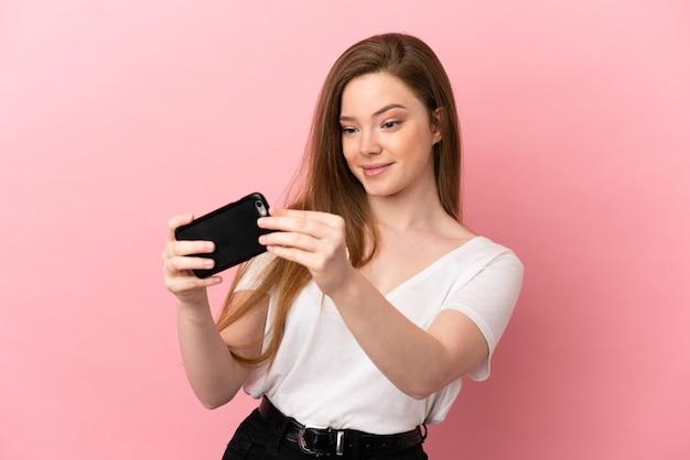 Девушка-подросток на изолированном розовом фоне играет с мобильным телефоном