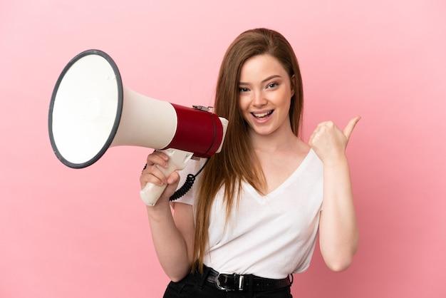 Девушка-подросток на изолированном розовом фоне кричит в мегафон и указывает сторону