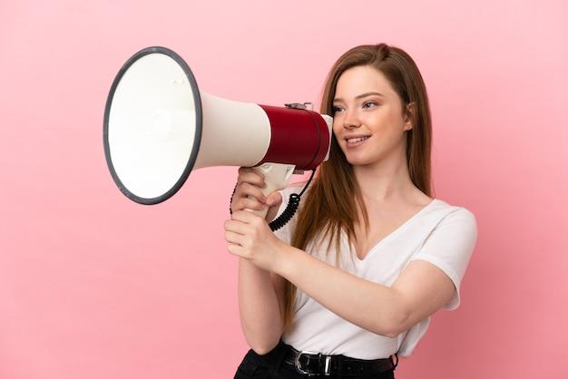 Девушка-подросток на изолированном розовом фоне кричит в мегафон, чтобы что-то объявить