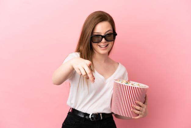 Девушка-подросток на изолированном розовом фоне в 3d-очках и держит большое ведро попкорна, указывая вперед