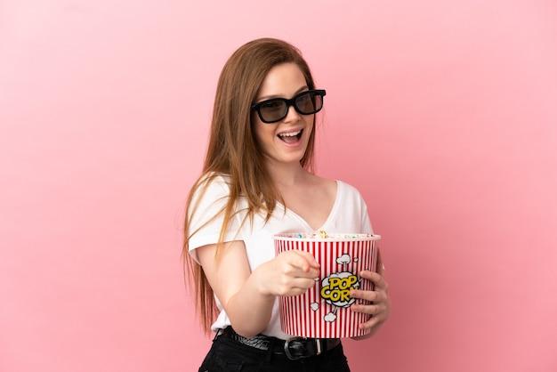 3d 안경을 쓰고 전면을 가리키는 동안 큰 팝콘 양동이를 들고 고립된 분홍색 배경 위에 있는 10대 소녀