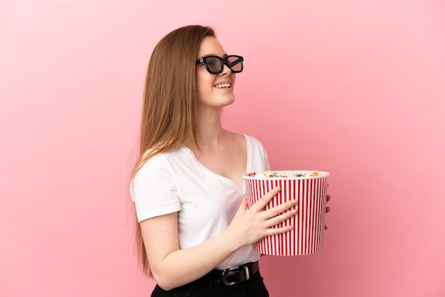 3d 안경을 쓰고 큰 팝콘 양동이를 들고 고립된 분홍색 배경 위에 있는 10대 소녀