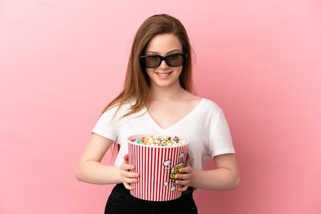 Девушка-подросток на изолированном розовом фоне в 3d-очках и держит большое ведро попкорна