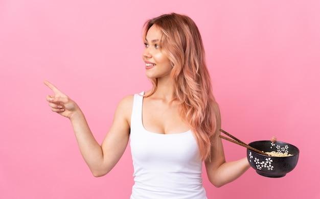 Девушка-подросток над изолированным розовым, указывая в сторону, чтобы представить продукт, держа миску лапши с палочками для еды