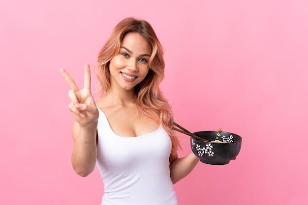 Девушка-подросток над изолированной розовой улыбкой и показывает знак победы, держа миску лапши с палочками для еды