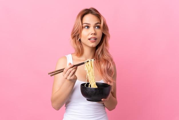 箸で麺のボウルを保持し、見上げる孤立したピンクの壁の上のティーンエイジャーの女の子