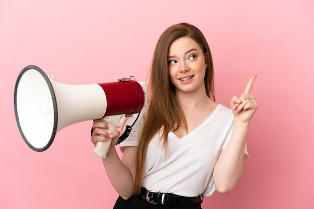 Девушка-подросток над изолированной розовой стеной держит мегафон и намеревается реализовать решение