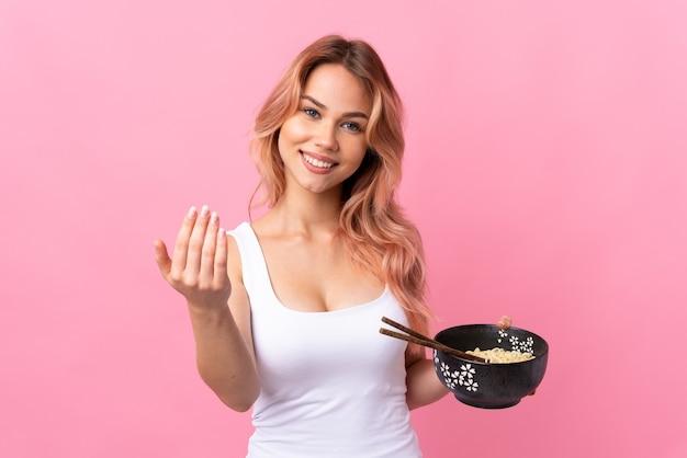 手で来るように誘う孤立したピンクの壁の上のティーンエイジャーの女の子。お箸で麺を持って来てくれて嬉しいです
