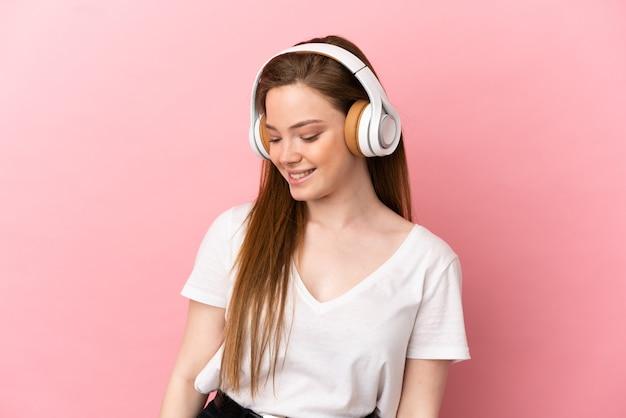 音楽を聞いて孤立したピンクの壁の上のティーンエイジャーの女の子