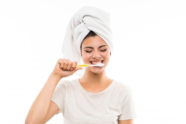 Девушка подростка над изолированной белой предпосылкой чистя ее зубы