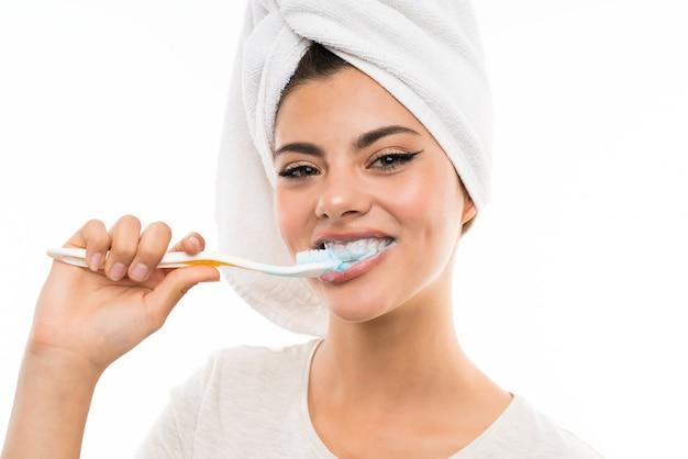 Девушка подростка над изолированной белизной чистя ее зубы щеткой