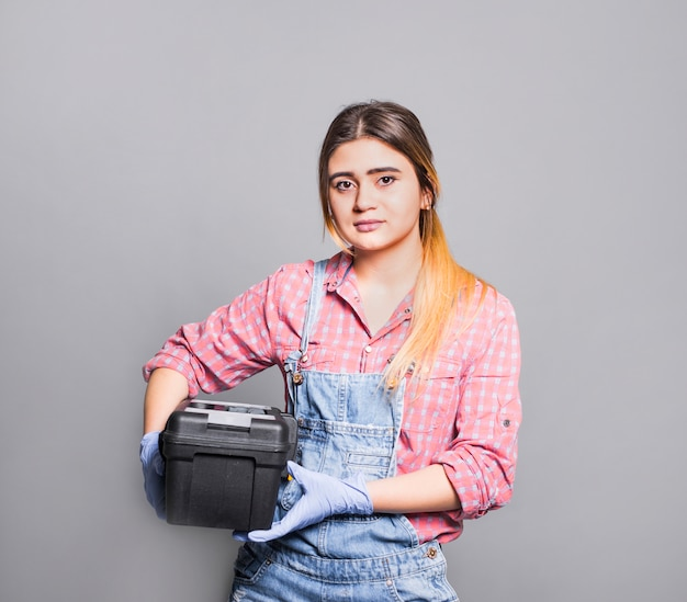 Teenager girl in overall with tool box