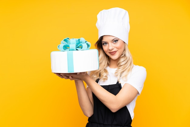 Teenager girl pastry holding a big cake isolated on yellow wall