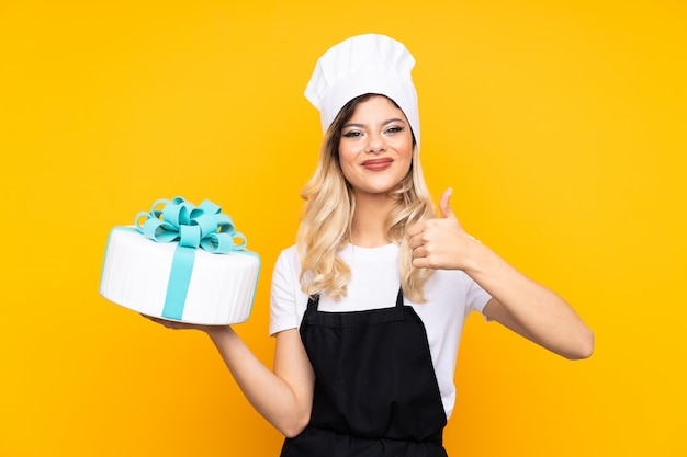 Teenager girl pastry holding a big cake on yellow wall giving a thumbs up gesture