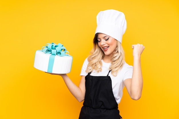 Teenager girl pastry holding a big cake on yellow wall making strong gesture