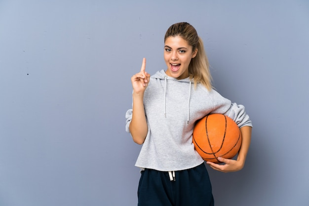 Teenager girl playing basketball over grey wall intending to realizes the solution while lifting a finger up