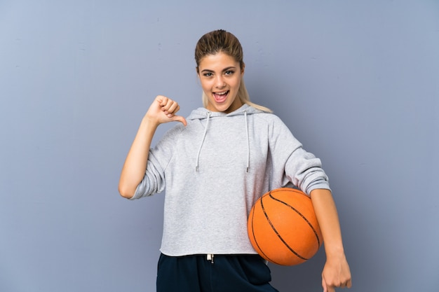 Teenager girl playing basketball over grey wall proud and self satisfied