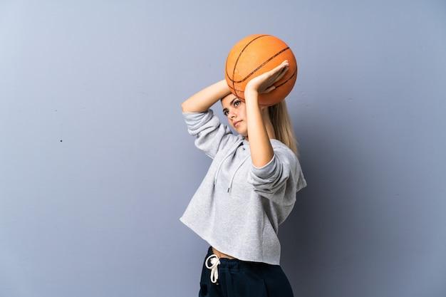 Teenager girl playing basketball over grey wall