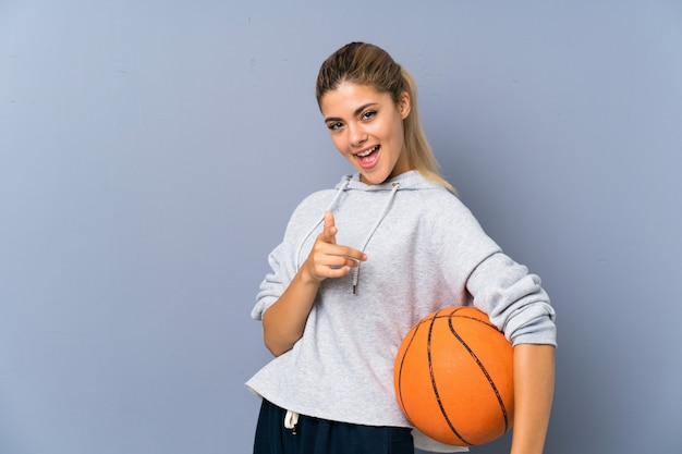Teenager girl playing basketball points finger at you with a confident expression