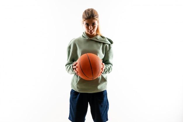 Teenager girl playing basketball