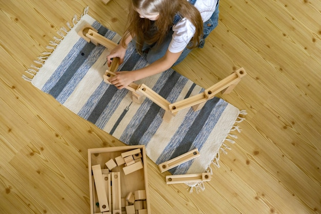 Teenager girl playing track constructor block tower with metallic ball maria montessori materials