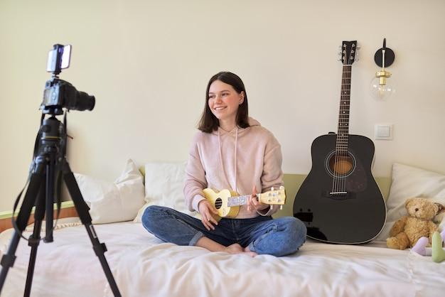 10代の少女は、ウクレレで音楽を演奏し、オンラインで学習し、フォロワーとチャットします。ミュージカル10代のブログ、vlog、チャンネル、現代のテクノロジー、若者のコンセプト