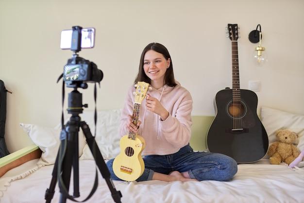 10代の少女は、ウクレレ、オンライン学習、フォロワーとのチャットで音楽を演奏します。ミュージカル10代のブログ、vlog、チャンネル、現代のテクノロジー、若者のコンセプト
