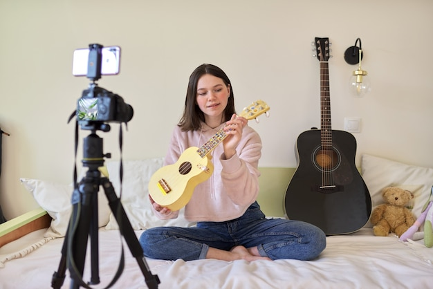 Teenager girl plays music on ukulele, online learning and chatting with followers. musical teenage blog, vlog, channel, modern technology, youth concept