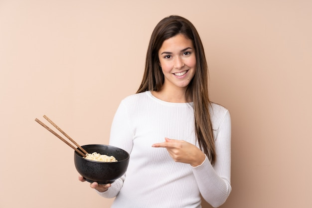 Teenager girl and pointing it while holding a bowl of noodles with chopsticks