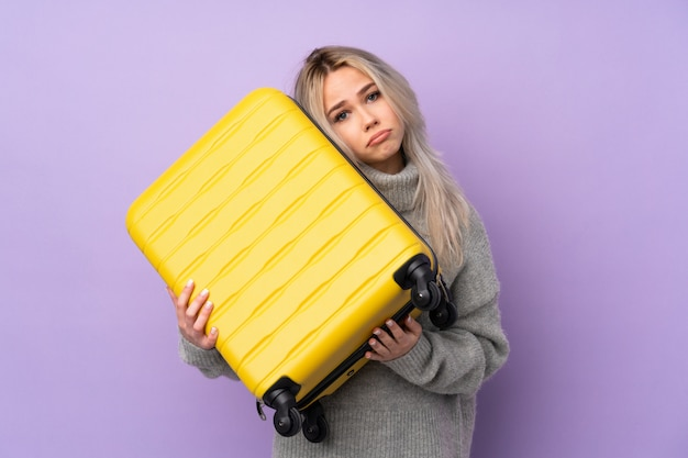 Teenager girl over purple wall in vacation with travel suitcase and unhappy
