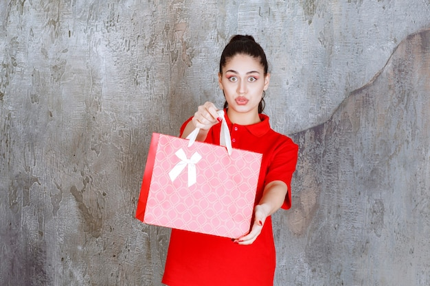 Ragazza adolescente in camicia rossa che tiene in mano una borsa della spesa rossa e la presenta