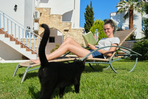 Teenager girl resting in backyard lying in sunbed reading book playing with black cat.