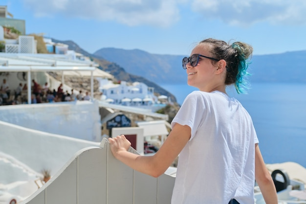Teenager girl resting on greek island santorini, female looking away, space white architecture of village oia, sea, sky in clouds, copy space