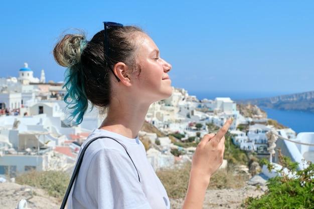 그리스 섬 산토리니에서 쉬고 있는 10대 소녀, 멀리 바라보는 여성, 이아 마을의 배경 흰색 건축물, 바다, 구름 속의 하늘, 복사 공간