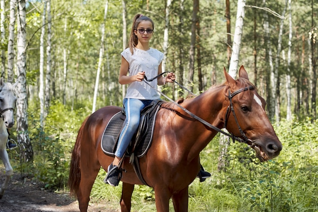 Teenager girl riding a brown horse, horseback riding for people in the park