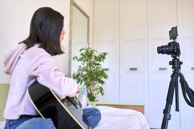 Девушка-подросток сидит дома на кровати с акустической гитарой, девушка играет на гитаре, записывая видео на камеру. технологии, социальные сети, искусство, хобби, подростковая концепция